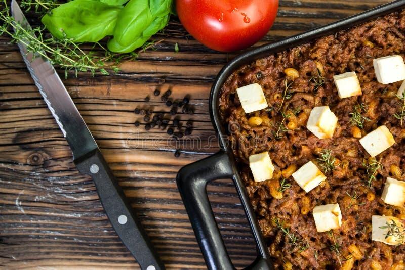 Τα ιταλικά μακαρόνια ψήνουν με τον κιμά και το τυρί φέτας σε έναν αγροτικό ξύλινο πίνακα που φωτογραφίζεται άνωθεν στοκ φωτογραφία με δικαίωμα ελεύθερης χρήσης