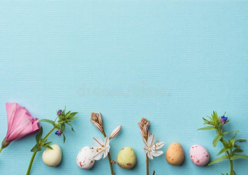 Τα κατώτατα σύνορα από τον πολύχρωμο speckled τομέα άνοιξη αυγών σοκολάτας ανθίζουν στο ανοικτό μπλε υπόβαθρο Πάσχα στοκ φωτογραφία