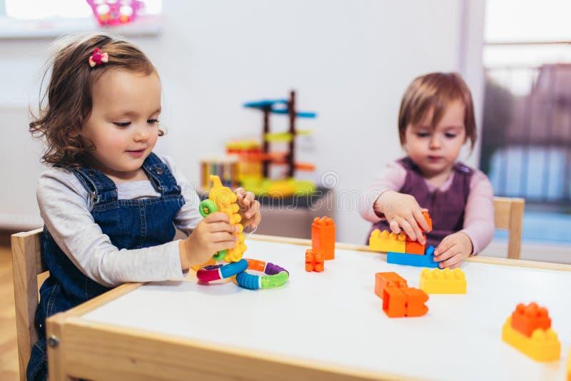Τα κορίτσια παιδιών παίζουν τα παιχνίδια στο σπίτι, τον παιδικό σταθμό ή το βρεφικό σταθμό στοκ εικόνα