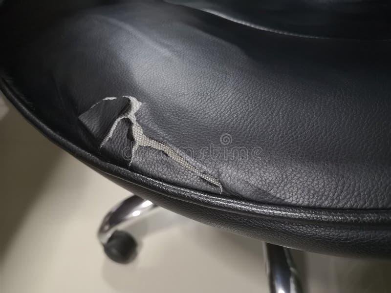 Τα μαύρα καθίσματα καρεκλών δέρματος έχουν βλαφθεί λόγω της επιδείνωσης Σχισμένος για να δει τον αφρό μέσα στοκ εικόνα