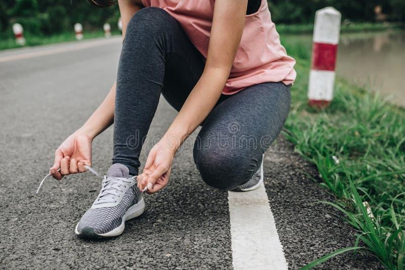 Τα νέα δένοντας τρέχοντας παπούτσια γυναικών ικανότητας σταθμεύουν δημόσια, υγιής έννοια τρόπου ζωής στοκ φωτογραφίες