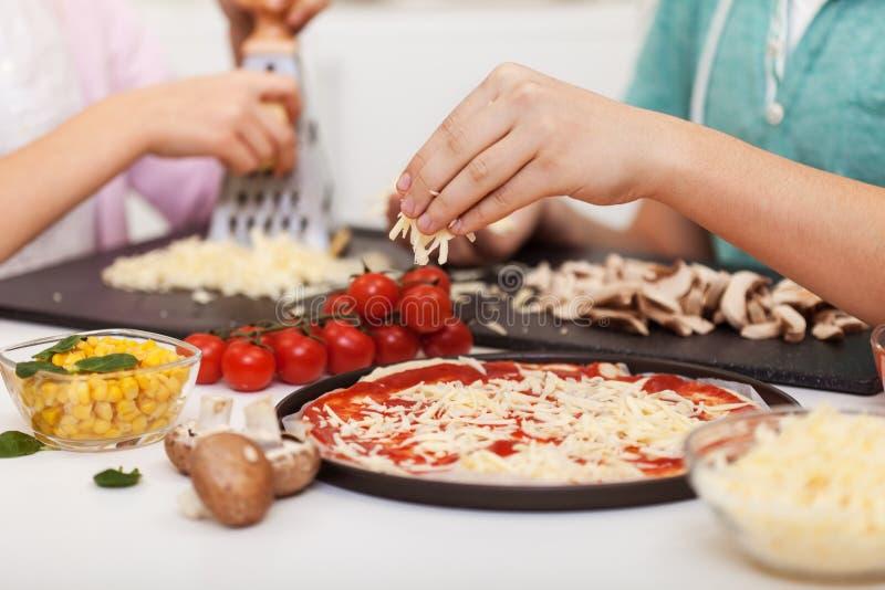 Τα νέα χέρια προετοιμάζουν την πίτσα στο σπίτι - σχάρα και ψεκάζουν το τυρί στοκ εικόνα