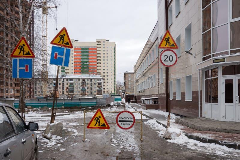 Τα οδικά σημάδια προειδοποίησης και τα σημάδια ορίου ταχύτητας στέκονται σε έναν διπλανό δρόμο στην είσοδο στο ναυπηγείο κατά τη  στοκ φωτογραφία με δικαίωμα ελεύθερης χρήσης