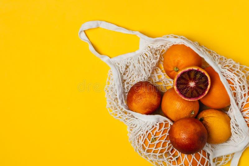 Τα οργανικά αιματηρά πορτοκάλια στο βαμβάκι παγιδεύουν την επαναχρησιμοποιήσιμη τσάντα, κίτρινο υπόβαθρο - ανακύκλωση, βιώσιμος τ στοκ εικόνα