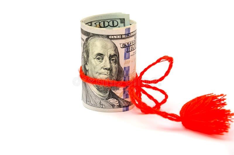 Τα δολάρια είναι στριμμένα και σχετισμένα με ένα κόκκινο τόξο σε ένα άσπρο υπόβαθρο στοκ φωτογραφίες με δικαίωμα ελεύθερης χρήσης