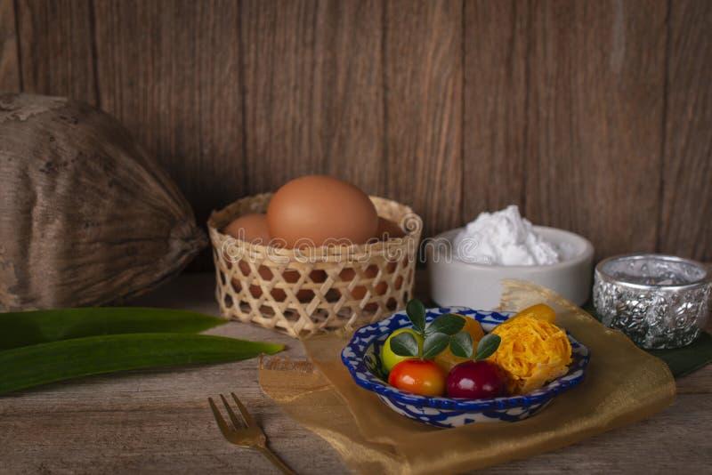 Τα ταϊλανδικά επιδόρπια σε ένα πιάτο των άσπρων και μπλε λωρίδων που τοποθετούνται στο χρυσό ύφασμα και τον ξύλινο πίνακα είναι ε στοκ φωτογραφία