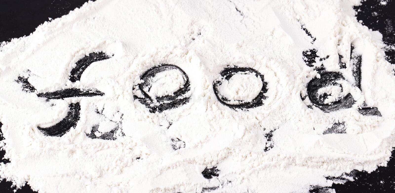 Τα τρόφιμα επιγραφής στο διεσπαρμένο άσπρο αλεύρι σίτου στοκ φωτογραφίες με δικαίωμα ελεύθερης χρήσης