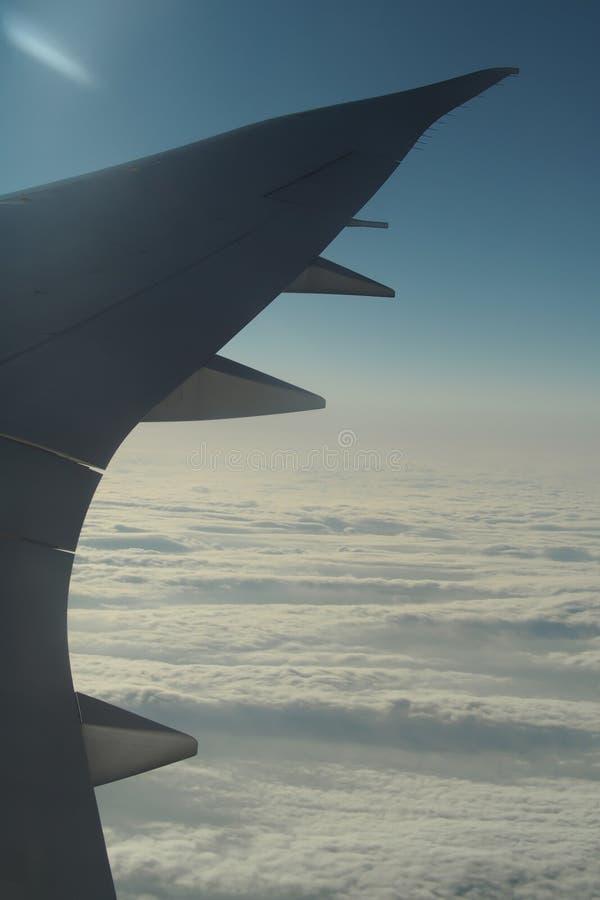 Τα φτερά του αεροπλάνου σε ένα υπόβαθρο σύννεφων και το φωτεινό ουρανό Στο βλαστό μέσω ενός παραθύρου αεροπλάνων στοκ φωτογραφία