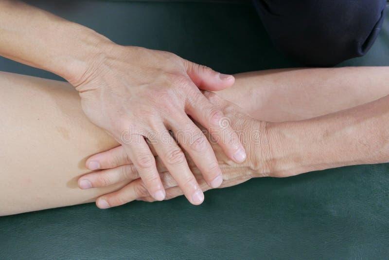 Τα φυσικά χέρια θεραπόντων μεταχειρίζονται το γόνατο στον ασθενή στοκ εικόνες με δικαίωμα ελεύθερης χρήσης