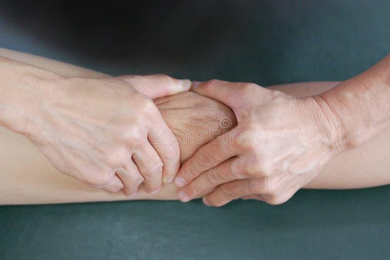 Τα φυσικά χέρια θεραπόντων μεταχειρίζονται το γόνατο στον ασθενή στοκ φωτογραφία με δικαίωμα ελεύθερης χρήσης
