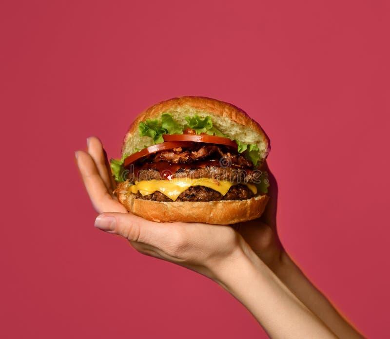 Τα χέρια γυναικών κρατούν το μεγάλο διπλό cheeseburger burger σάντουιτς με τις ντομάτες και το τυρί βόειου κρέατος στοκ φωτογραφία