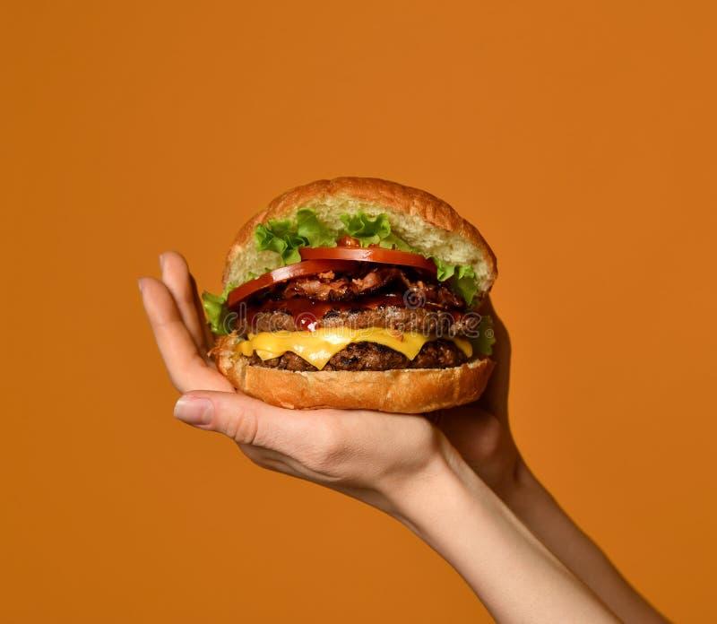 Τα χέρια γυναικών κρατούν το μεγάλο cheeseburger burger σάντουιτς με το μαρμάρινο βόειο κρέας και το μπέϊκον σε κίτρινο στοκ εικόνες