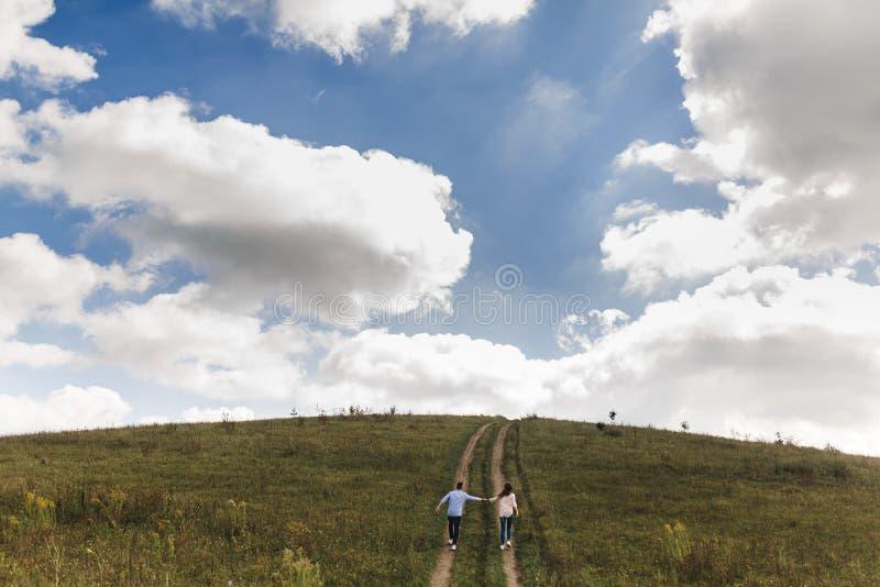 Τα χέρια εκμετάλλευσης ζεύγους περπατούν μακριά Πορτρέτο ενός ρομαντικών νεαρού άνδρα και μιας γυναίκας ερωτευμένων στη φύση στοκ εικόνες