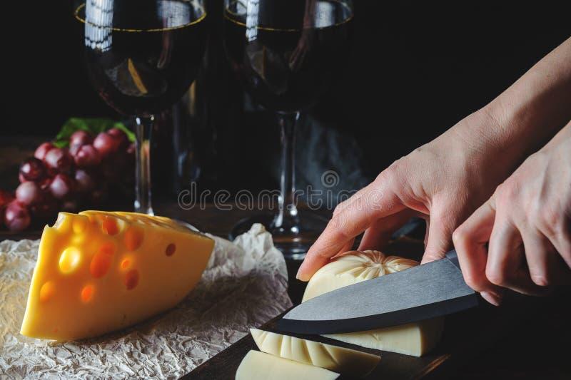 Τα χέρια κόβουν το τυρί στο κρασί στοκ εικόνες με δικαίωμα ελεύθερης χρήσης