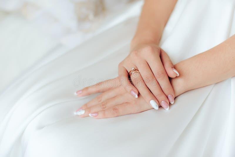 Τα χέρια της νύφης σε ένα λευκό ντύνουν με ένα όμορφο μανικιούρ 1 στοκ εικόνα