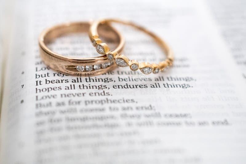 Τα χρυσά γαμήλια δαχτυλίδια στο στίχο Βίβλων, αγάπη δεν αποτυγχάνουν ποτέ στοκ φωτογραφία με δικαίωμα ελεύθερης χρήσης