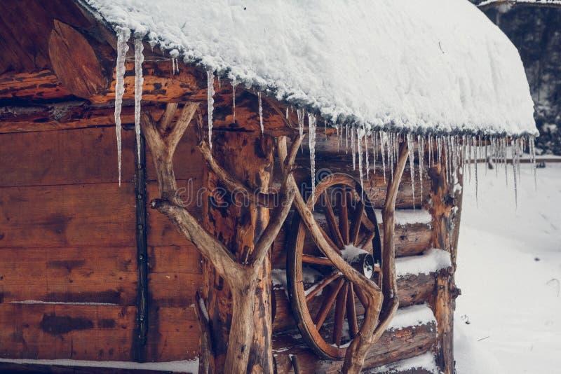 Τα παγάκια κρεμούν από τη στέγη ενός ξύλινου σπιτιού στο δάσος κοντά στην τέφρα βουνών στοκ εικόνες