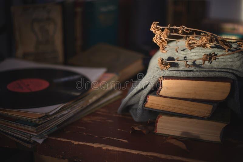 Τα παλαιά βιβλία που καλύπτονται με ένα ύφασμα με ένα ξηρό λουλούδι στην κορυφή βρίσκονται στον πίνακα και ένα παλαιό βινυλίου αρ στοκ εικόνες με δικαίωμα ελεύθερης χρήσης