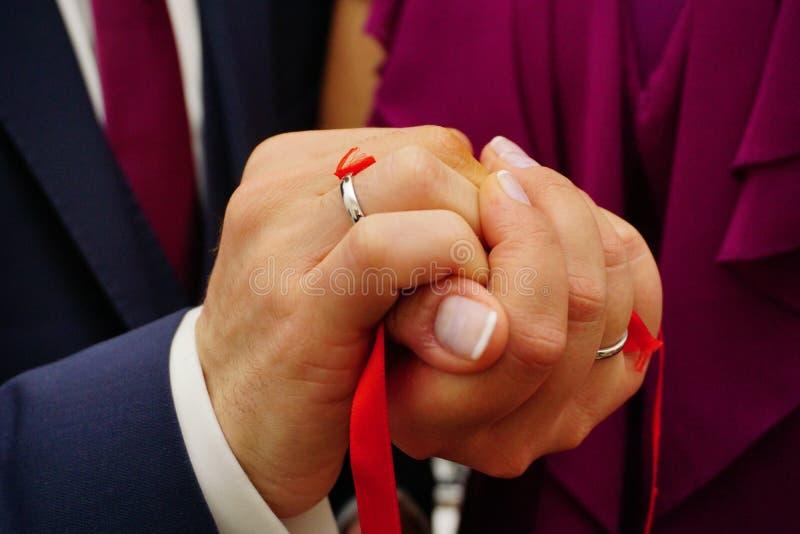 Τα πρόσφατα δεσμευμένα χέρια ζευγών με την κορδέλλα κοντά επάνω βλέπουν στοκ φωτογραφίες με δικαίωμα ελεύθερης χρήσης