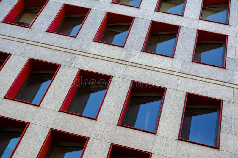Τεμάχιο της σύγχρονης πρόσοψης οικοδόμησης με τα κόκκινα πλαίσια παραθύρων στοκ εικόνα