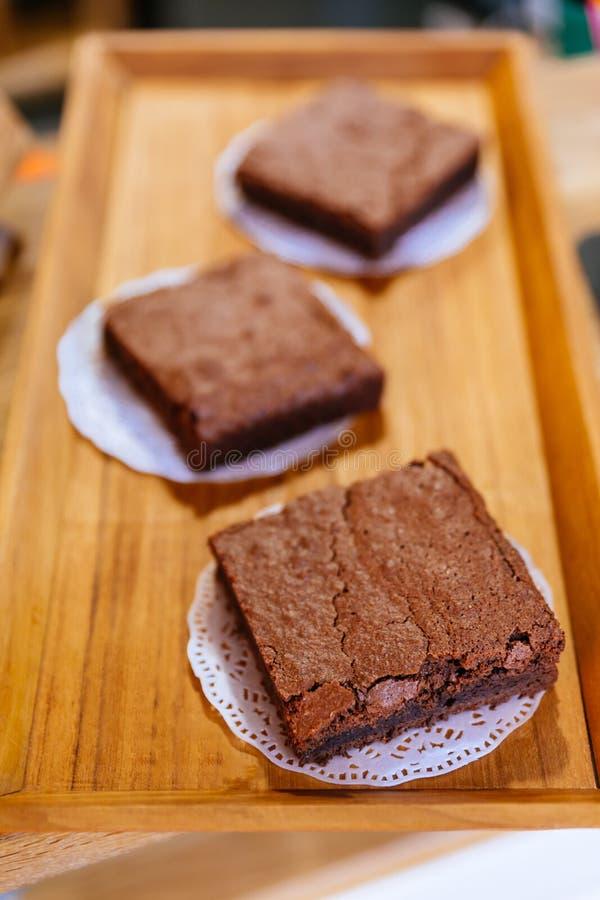 Τετραγωνικά Brownie κέικ σοκολάτας στον ξύλινο δίσκο που έτοιμο να πωλήσει Λειωμένο μέταλλο στο στόμα σας στοκ φωτογραφίες