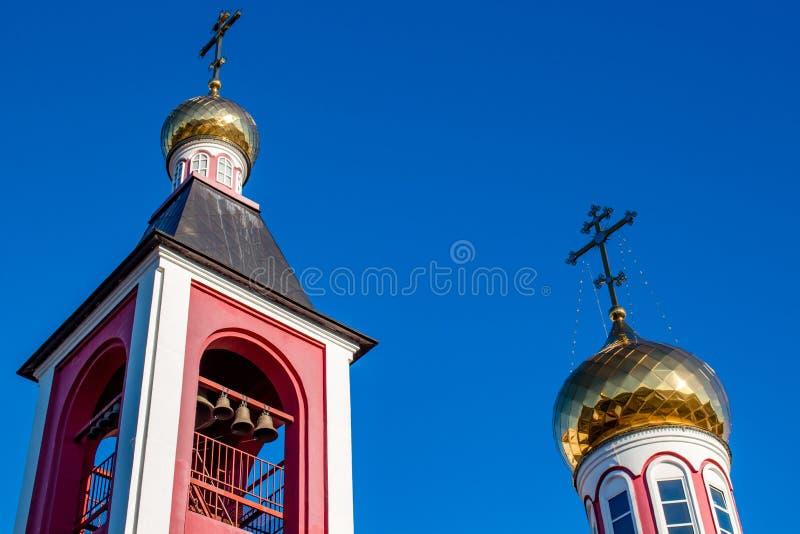 Τετραγωνικοί πύργος κουδουνιών και θόλοι της ρωσικής Ορθόδοξης Εκκλησίας με τους σταυρούς στοκ φωτογραφίες