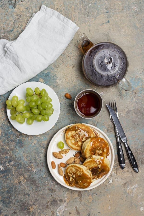 Τηγανίτες με την καραμέλα και καρύδια με το σταφύλι και το τσάι στοκ φωτογραφία με δικαίωμα ελεύθερης χρήσης