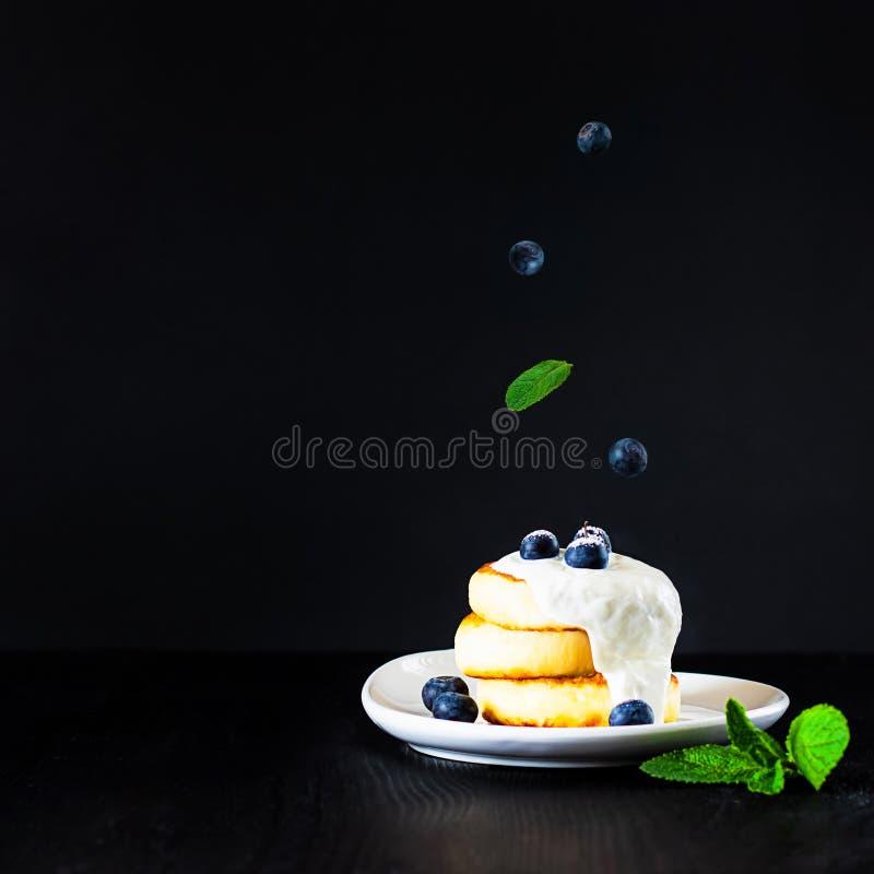 Τηγανίτες τυριών εξοχικών σπιτιών που ολοκληρώνονται με την κρέμα, τα βακκίνια και τη σκόνη ζάχαρης με τα μειωμένα μούρα και το φ στοκ εικόνες