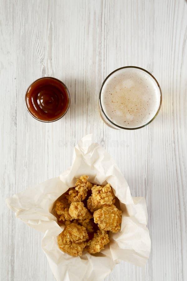 Τηγανισμένα δαγκώματα κοτόπουλου στο κιβώτιο εγγράφου, σάλτσα σχαρών, ποτήρι της μπύρας πέρα από την άσπρη ξύλινη επιφάνεια, τοπ  στοκ φωτογραφίες με δικαίωμα ελεύθερης χρήσης