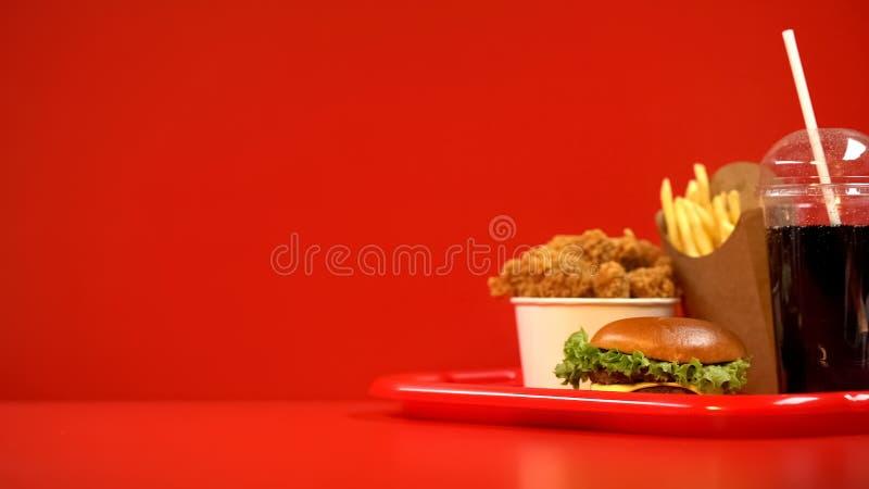 Τηγανισμένα χάμπουργκερ τηγανιτών πατατών φτερών και ποτό σόδας στον κόκκινο δίσκο, take-$l*away τρόφιμα στοκ φωτογραφία