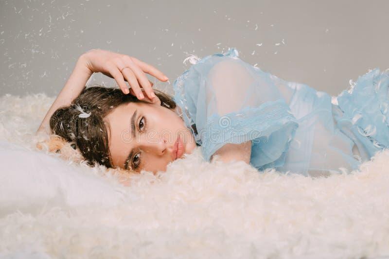 την ονειρεύεται που χάνε&t Όμορφο κορίτσι στις μεταξωτές πυτζάμες με το φτερό σε μακρυμάλλη Χαριτωμένη χαλάρωση κοριτσιών στο μαξ στοκ εικόνες με δικαίωμα ελεύθερης χρήσης