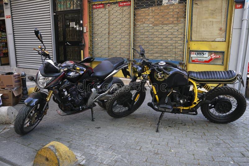 Τη μοτοσικλέτα της Honda και μια άγνωστη μοτοσικλέτα ύφους δρομέων καφέδων σταθμεύουν στοκ εικόνα με δικαίωμα ελεύθερης χρήσης