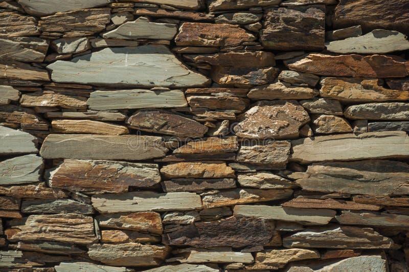 Τοίχος φιαγμένος από πέτρα πλακών που κάνει ένα περίεργο σχέδιο στοκ φωτογραφίες