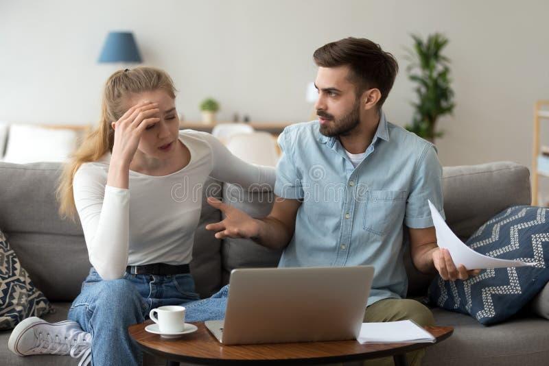Τονισμένο δυστυχισμένο ζεύγος που υποστηρίζει για τις δαπάνες με το lap-top και τα έγγραφα στοκ φωτογραφία