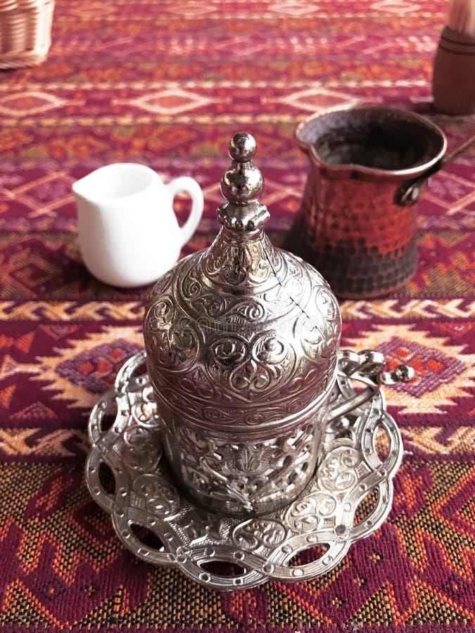 Τουρκικός καφές στο φλυτζάνι μετάλλων με τις διακοσμήσεις στο κόκκινο υπόβαθρο στοκ φωτογραφία