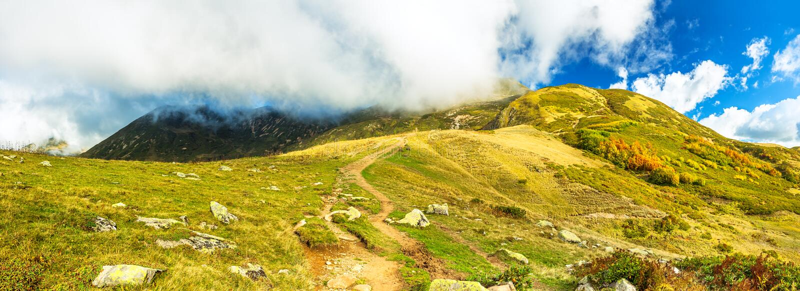 Τοπίο βουνών πανοράματος με το μπλε ουρανό και τα άσπρα σύννεφα στοκ φωτογραφία με δικαίωμα ελεύθερης χρήσης