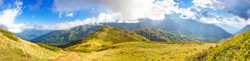 Τοπίο βουνών πανοράματος με το μπλε ουρανό και τα άσπρα σύννεφα στοκ εικόνες