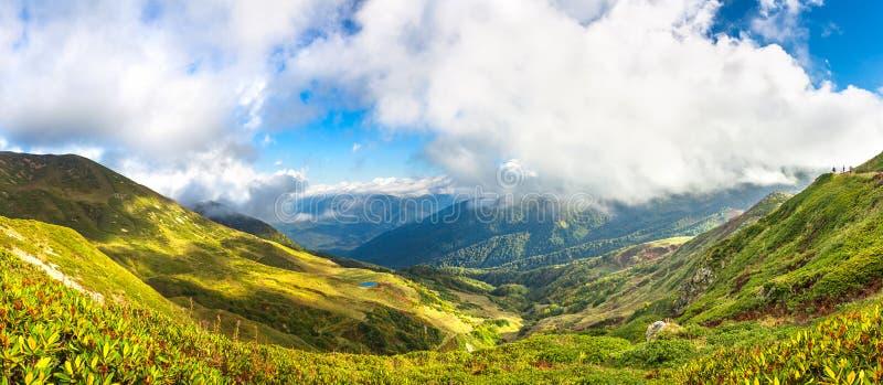 Τοπίο βουνών πανοράματος με το μπλε ουρανό και τα άσπρα σύννεφα στοκ εικόνα με δικαίωμα ελεύθερης χρήσης