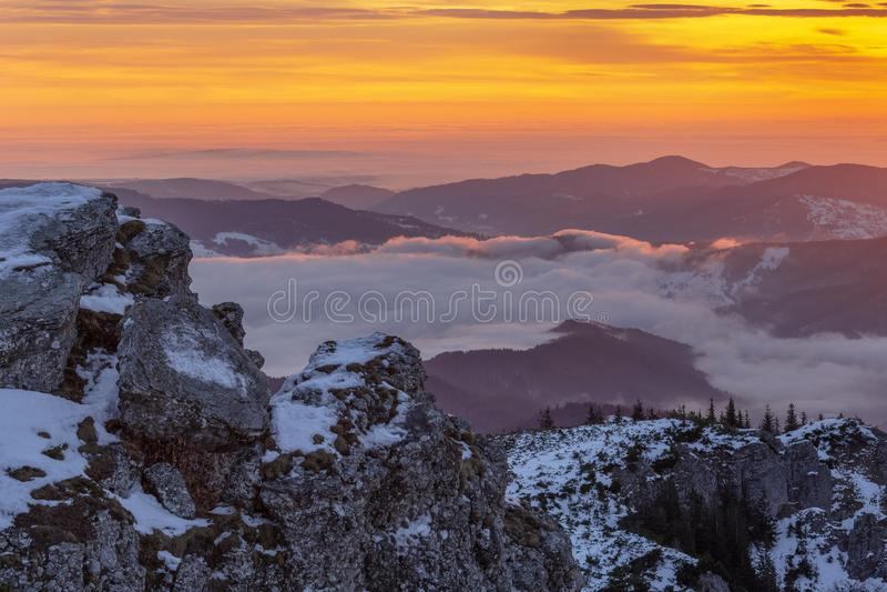 Τοπίο της ομορφιάς του χειμώνα στα χιονώδη βουνά μια πολύ κρύα ημέρα με την ομίχλη και ακτίνες του φωτός στο δάσος στοκ εικόνα