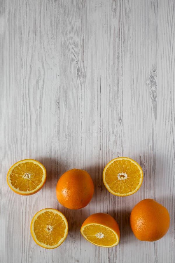 Τοπ άποψη, διχοτομημένα και ολόκληρα πορτοκάλια στο άσπρο ξύλινο υπόβαθρο, τοπ άποψη Υπερυψωμένος, άνωθεν, επίπεδος βάζει διάστημ στοκ φωτογραφίες