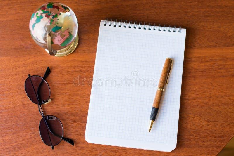 Τοπ άποψη της κενών Λευκής Βίβλου σημειωματάριων και της σφαίρας, μαύρα γυαλιά, παγκόσμιος χάρτης στο ξύλινο υπόβαθρο με το διάστ στοκ φωτογραφίες