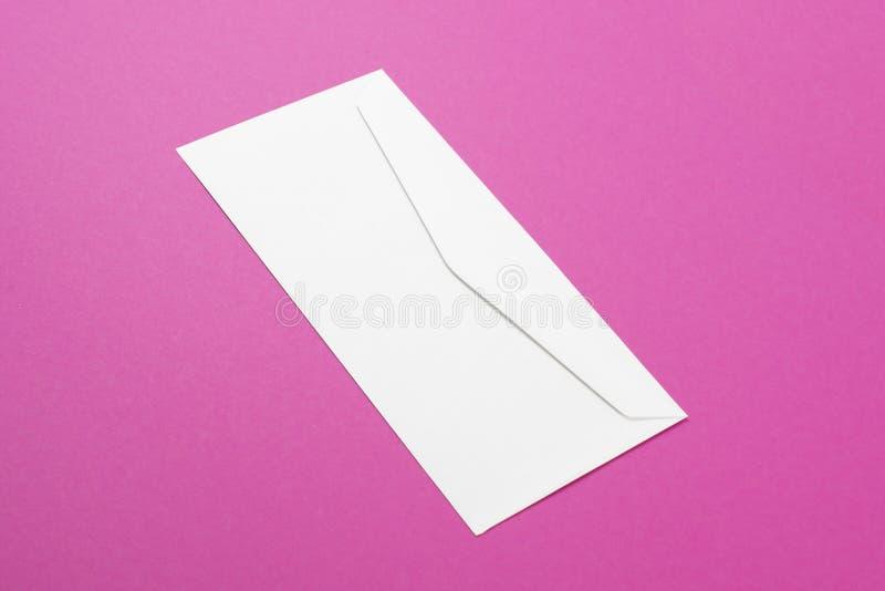 Τοπ άποψη του άσπρου κενού φακέλου στο ρόδινο υπόβαθρο Ελάχιστη έννοια Μοντέρνο χρώμα στοκ φωτογραφία με δικαίωμα ελεύθερης χρήσης