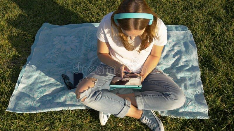 Τοπ άποψη του νέου θηλυκού με τις συσκευές και τα ακουστικά στο πάρκο στην πράσινη χλόη στοκ εικόνες