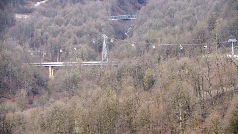 Τοπ άποψη του τελεφερίκ πέρα από τη γέφυρα Περάσματα τελεφερίκ μέσω του άγριου δάσους έξω από την πόλη το φθινόπωρο Δασική περιοχ στοκ εικόνες