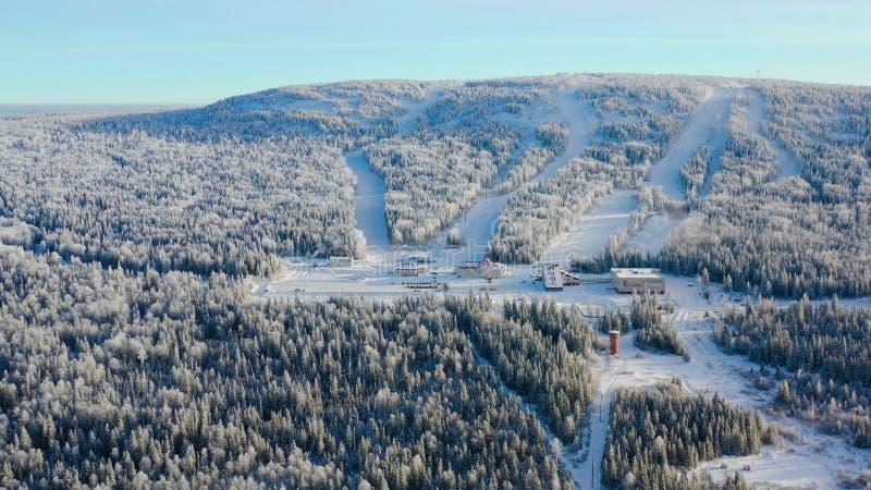 Τοπ άποψη του χιονοδρομικού κέντρου στο πόδι του βουνού footage Το απομονωμένο χιονοδρομικό κέντρο στο πόδι του λόφου με τις κλίσ στοκ φωτογραφία