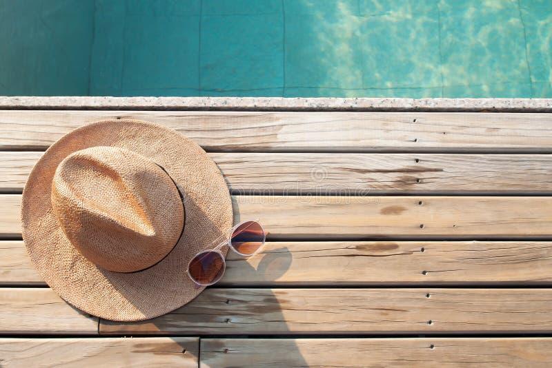 Τοπ άποψη του poolside, του καπέλου ήλιων και των γυαλιών ηλίου στο ξύλινο πάτωμα στοκ φωτογραφία