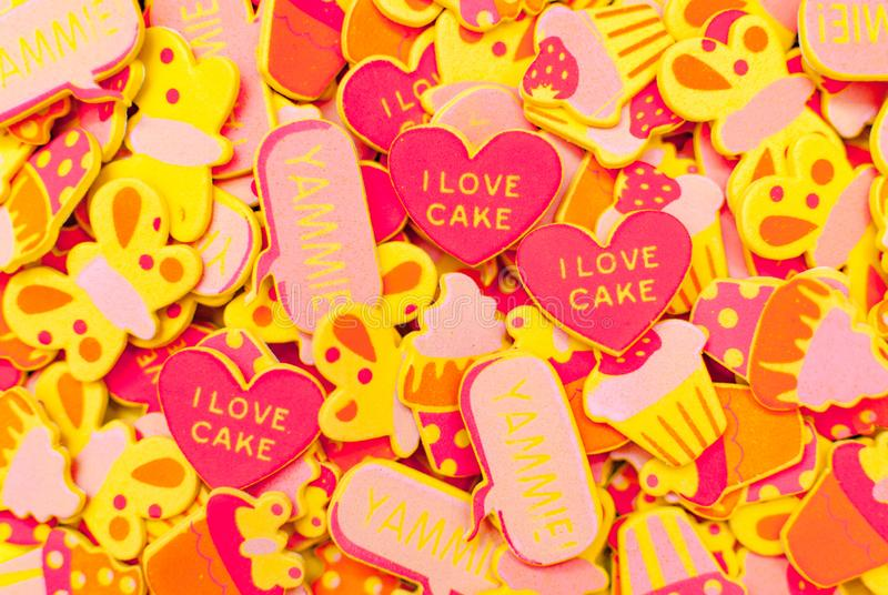 Τοπ άποψη των μερών των καραμέλα-χρωματισμένων αυτοκόλλητων ετικεττών αφρού που απεικονίζουν τις καρδιές, πεταλούδες και cupcakes στοκ φωτογραφία με δικαίωμα ελεύθερης χρήσης