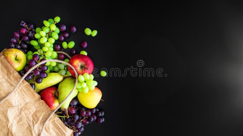 Τοπ άποψη των φρέσκων οργανικών τοπικών φρούτων στην τσάντα καφετιού εγγράφου στο σκοτεινό υπόβαθρο στοκ φωτογραφία με δικαίωμα ελεύθερης χρήσης