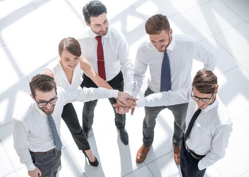 Τοπ όψη νέοι υπάλληλοι που διπλώνουν τα χέρια τους από κοινού στοκ φωτογραφία