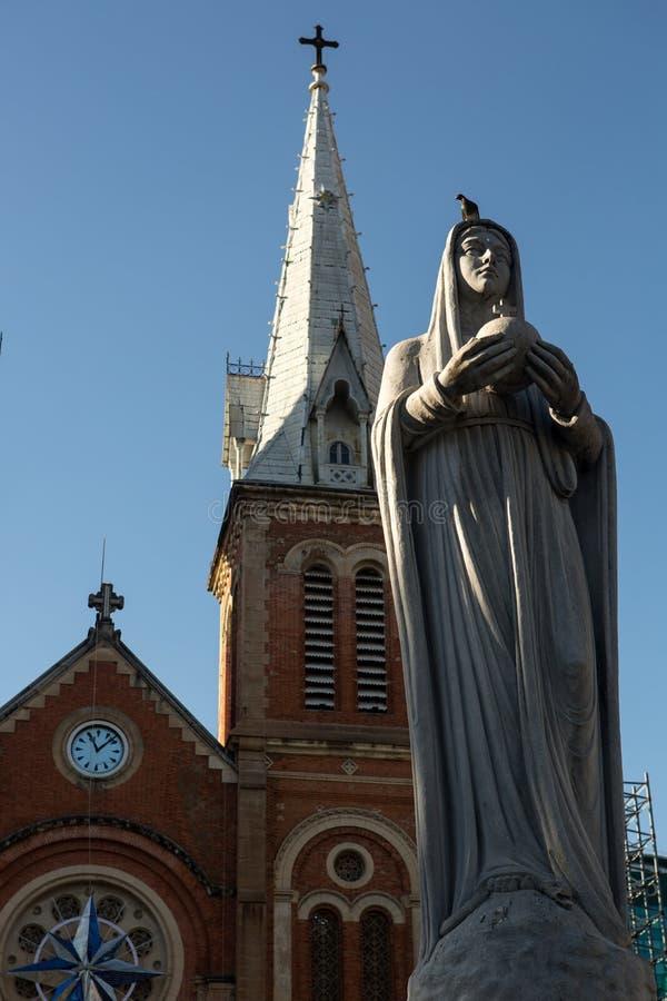 Το άγαλμα της Virgin Mary και το εξωτερικό της βασιλικής καθεδρικών ναών Saigon Notre Dame στην πόλη του Ho Chi Minh, Βιετνάμ Ασί στοκ φωτογραφία
